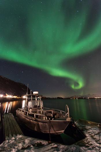 Boat moored at beach against aurora borealis at night