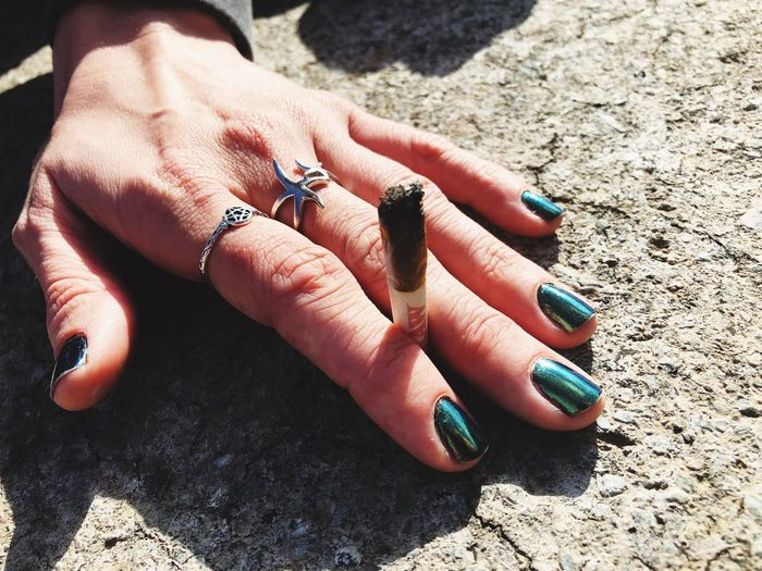 Cropped Image Of Woman Holding Marijuana Joint While Sitting On Rock