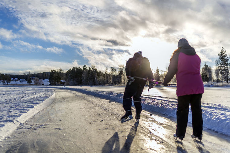 Rear view of people ice skating on road during winter