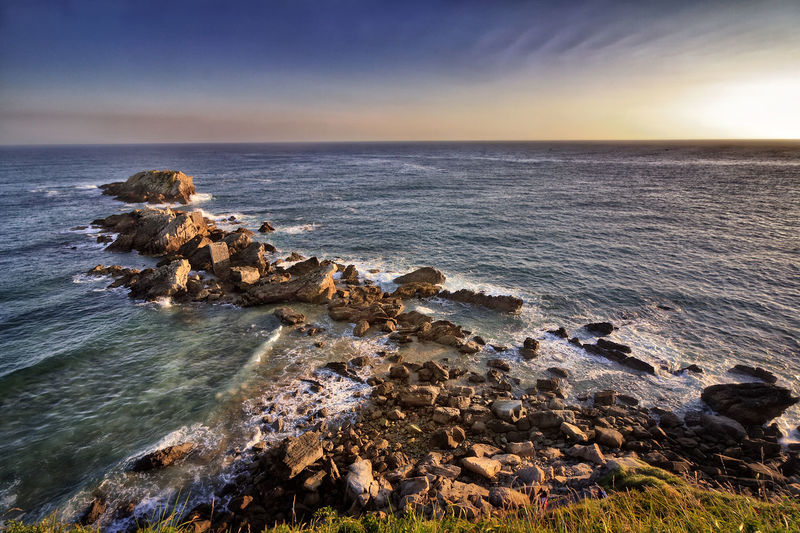 Scenic view of sea by rocks against sky during sunset