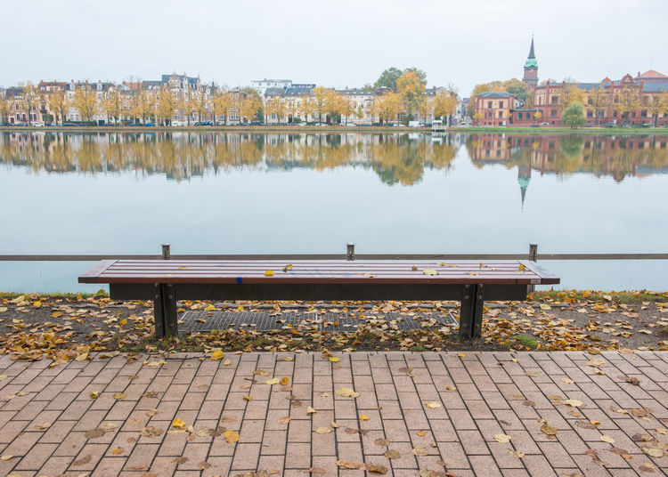 Wooden bench at Schwerin city Built Structure Bench Water Architecture Day Nature River Seat Building Exterior City No People Sky Empty Reflection Outdoors Park Plant Building Park Bench Change