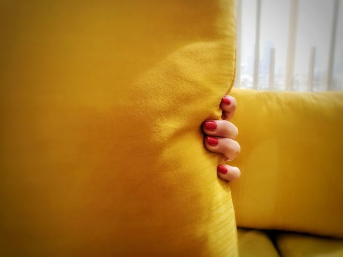 Cropped Hand Of Woman Holding Yellow Pillow
