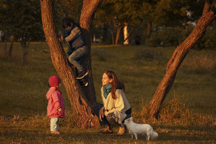 Siblings playing on tree trunk