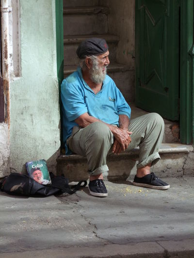 Revolunista, Obispo Street Composition Contemplation Cuba Growing Old HERO Havana Sunlight And Shade Bearded Book Cap Capital City Depression - Sadness Full Frame Hopelessness Outdoor Photography Poverty Revolunista Senior Adult Senior Citizen  Sitting Social Issues This Is Aging Unemployment