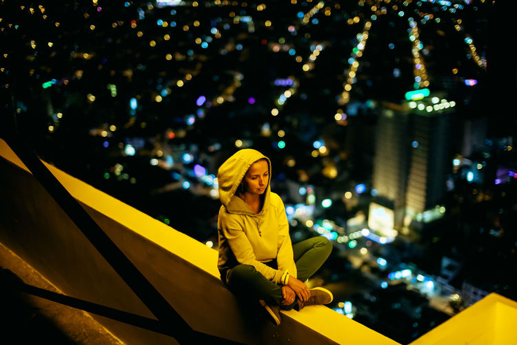 Woman sitting on retaining wall against illuminated city at night