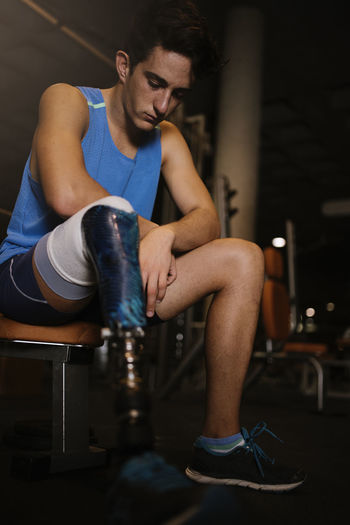 Man with artificial leg sitting in gym