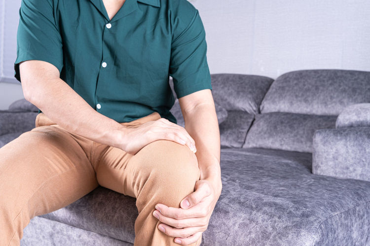 Midsection of man suffering from knee pain