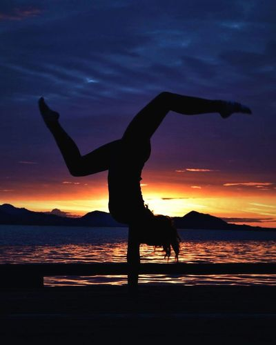 Sunset Silhouette Healthy Lifestyle Balance Sea One Person Strength Practicing Vitality Exercising Water Lifestyles Full Length Outdoors People Flexibility Night Beauty In Nature Adults Only Nature Live For The Story