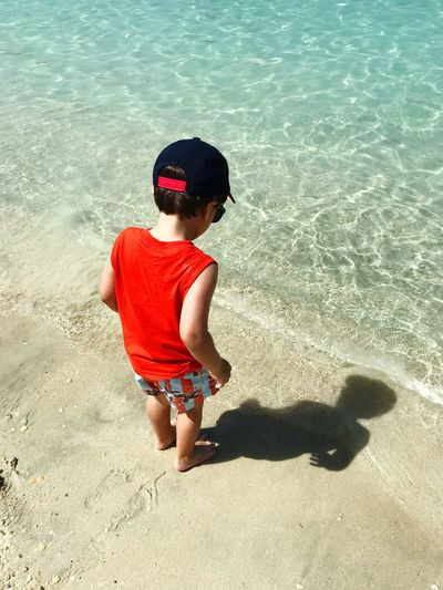 High Angle View Of Boy Standing On Shore At Beach During Summer