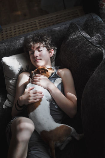 Boy with dog sleeping on sofa at home
