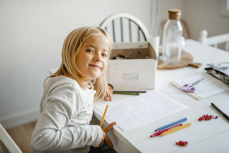 Portrait of girl sitting on table at home