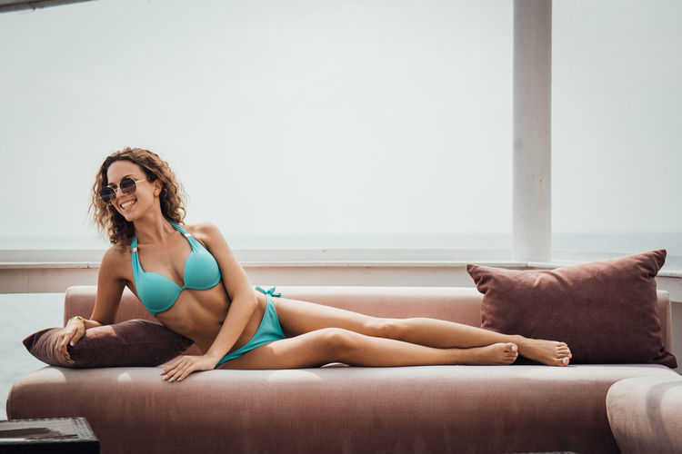 Full length of woman relaxing on sofa