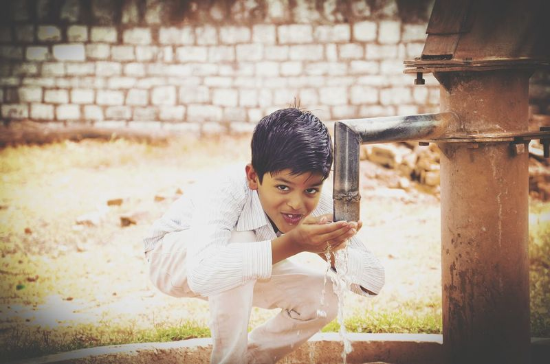 Portrait of boy drinking water from water pump