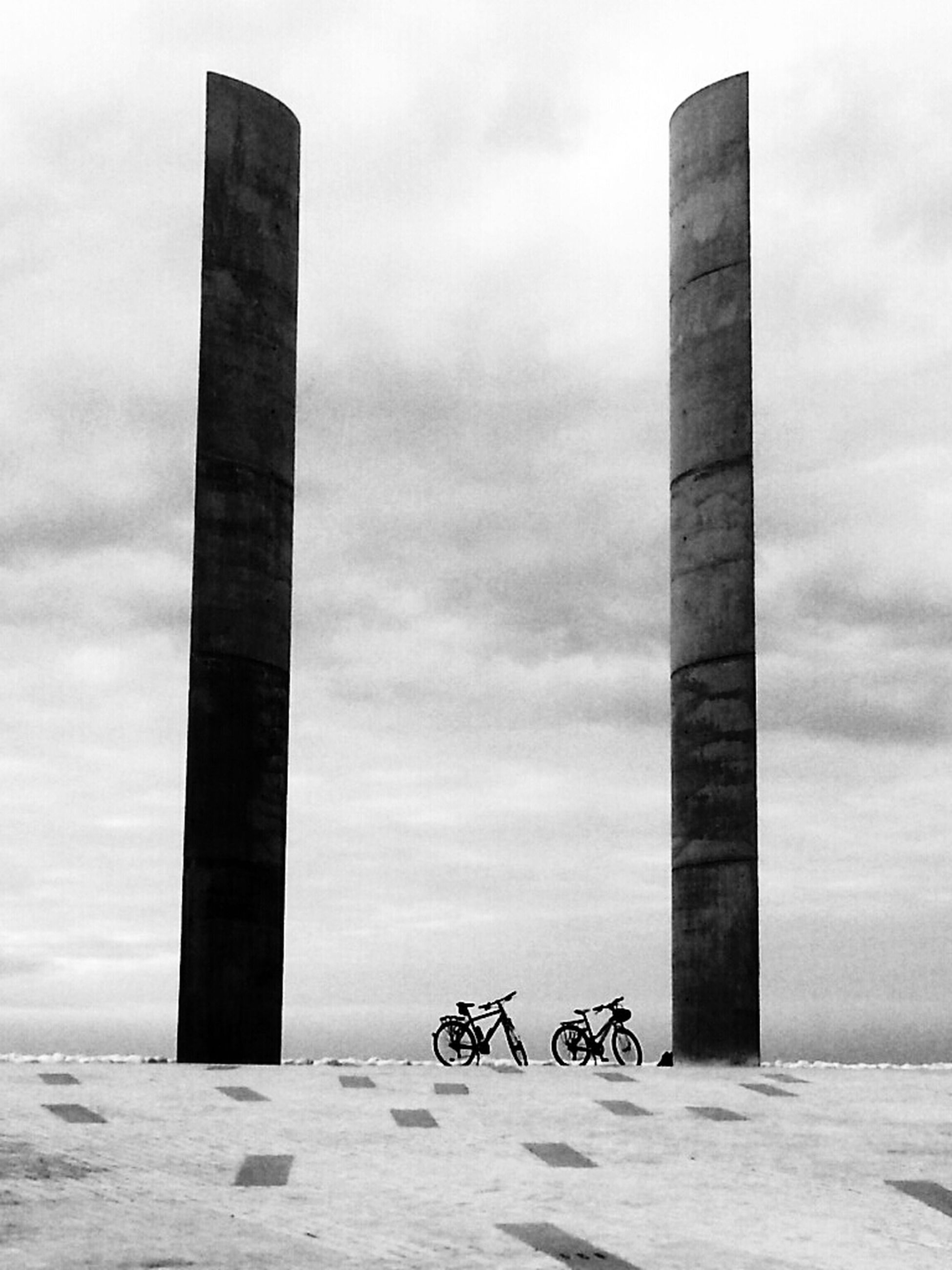 sky, cloud - sky, beach, built structure, architecture, day, sea, cloudy, outdoors, sand, cloud, tranquility, pole, wood - material, building exterior, nature, shore, protection, bicycle, weather