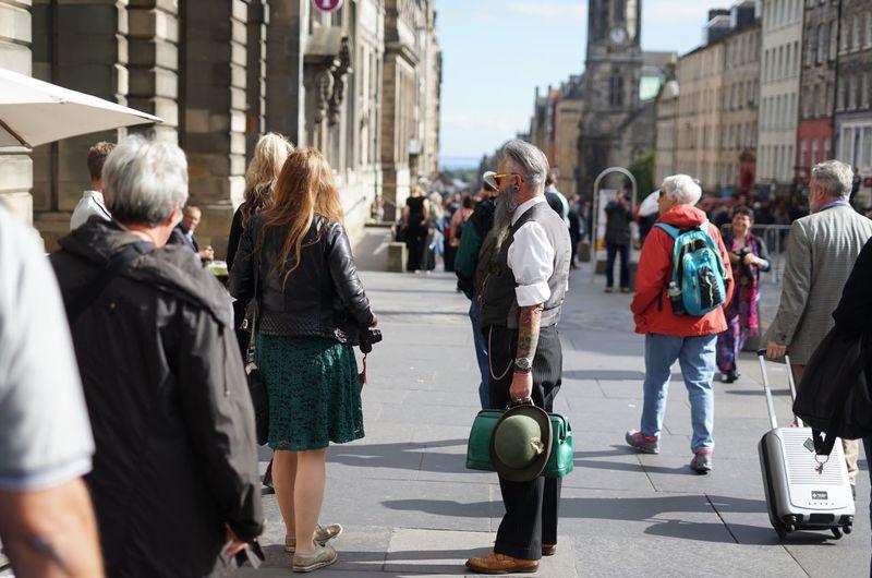 Rear view of people walking on road along buildings