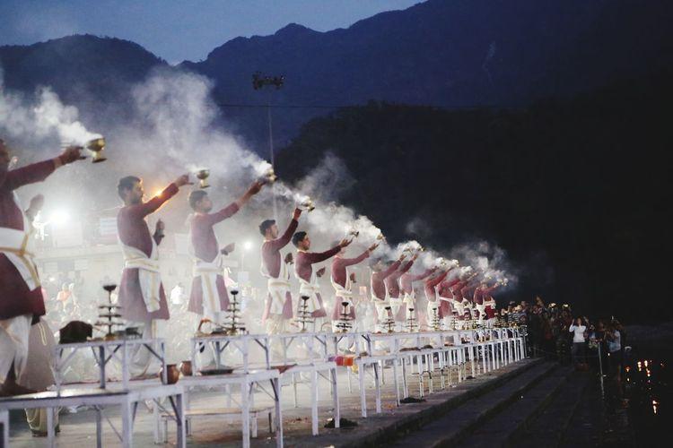 People performing ganga aarti ceremony held on edge of ganges river against sky