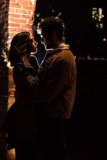 Young Couple Embracing While Standing Outdoors At Night