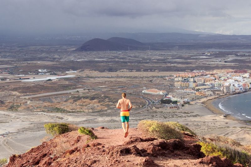 Rear View Of Shirtless Man Running On Landscape