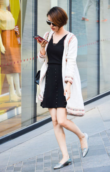 Adult Adults Only Casual Clothing Day Fashion Full Length Holding Indoors  Leisure Activity Lifestyles One Person One Young Woman Only People Purse Real People Retail  Shopping Bag Technology Wireless Technology Women Young Adult Young Women