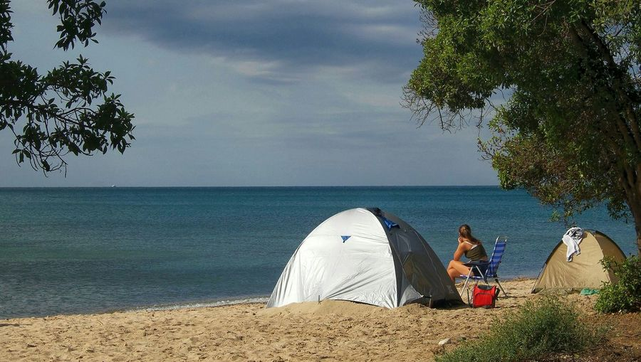 Woman Sitting On Chair By Tent On Beach