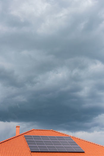 Red tile roof with photovoltaic panels during stormy weather solar pv installation and dark blue sky