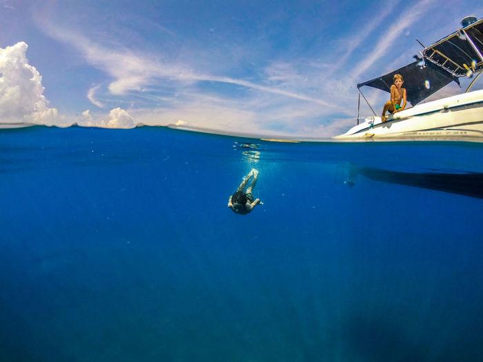 Man swimming in sea against sky