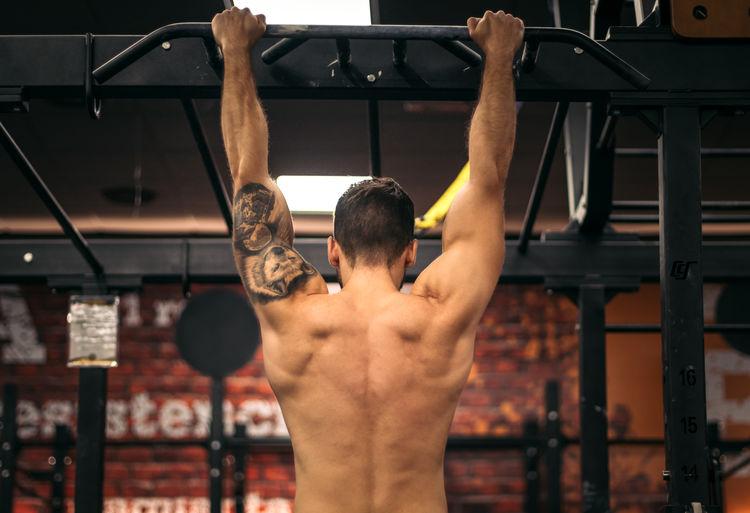 Rear view of shirtless man looking at store
