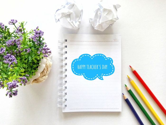 High angle view of text on diary by colored pencils at table