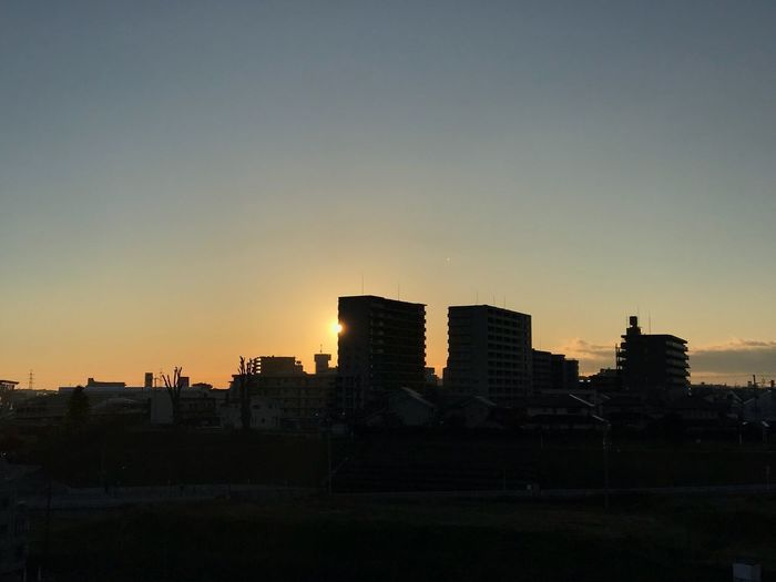 Cityscape against clear sky during sunset