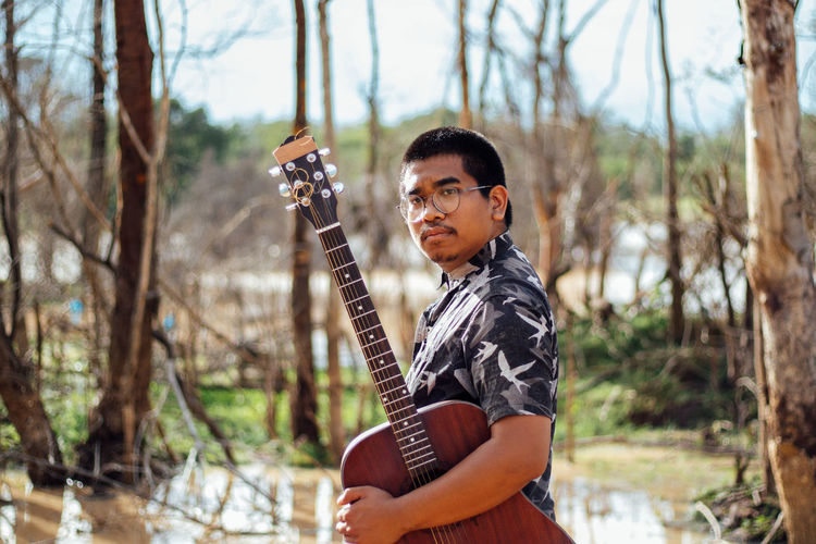 Portrait of young man holding guitar standing in park