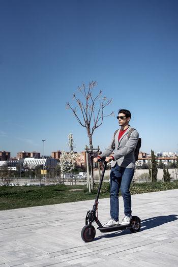Full length portrait of man against blue sky