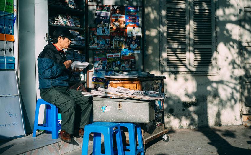 Man sitting on stool at shop