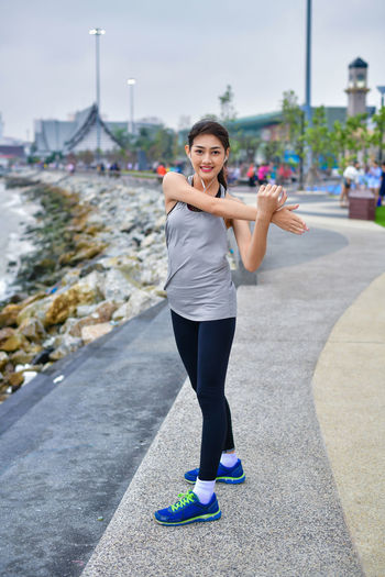 Sports concept. Beautiful girl is exercising on the beach with warm up. Beautiful girl is happy to exercise. Beautiful girls like to exercise by warm up. People are exercising on the beach. Terrestrial Sports Active Activities Activity Asian  Athlete Blue Body Clothes Exercise Exert Female Fit Fitness Freedom Freelife Girl Happiness Happy HEAL Health Healthcare Healthful Healthy Japanese  Legs Lifestyle Loosen Morning Muscles Ocean Relax Relaxation Resilient Runner Running Sea Seaside Sky Sports Stretch Trail Training Up Walking Warm Warm Body Warm Up Woman Young