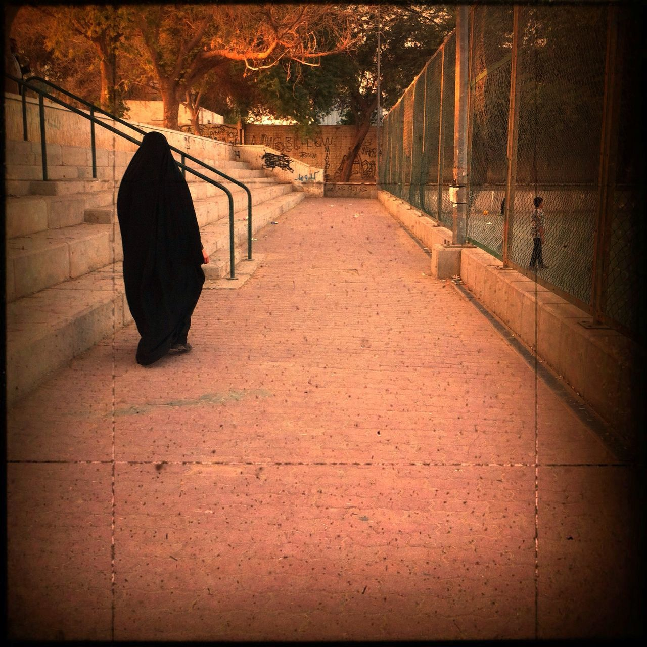 Rear view of a woman in burka walking on pathway