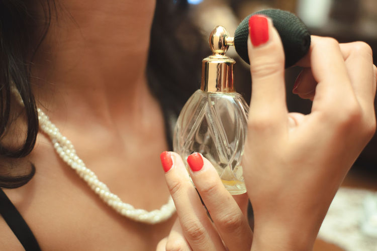 Midsection of woman holding perfume