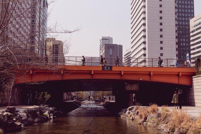 Footbridge over city against clear sky