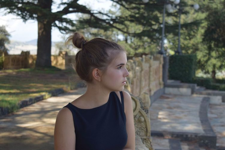 Teenage girl looking away while standing outdoors