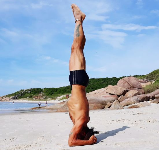 Side view full length of shirtless man doing headstand at beach
