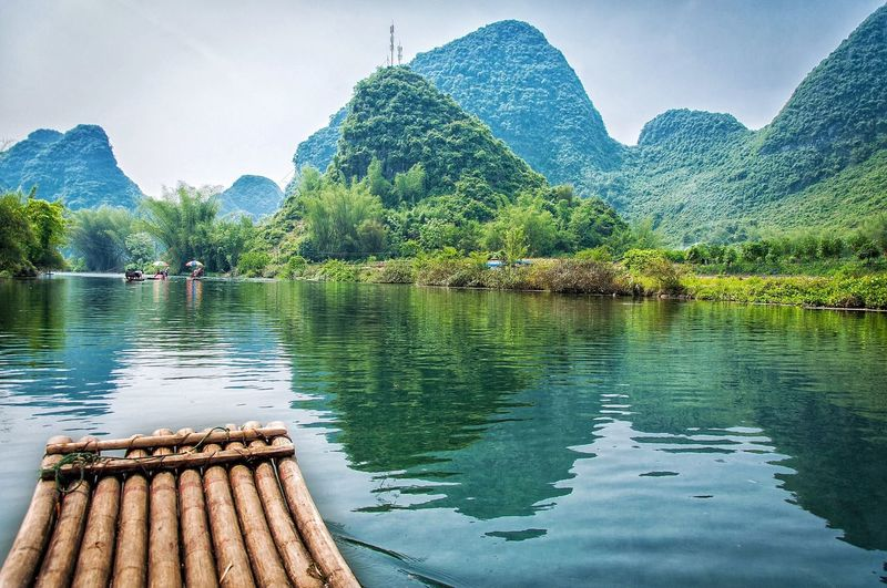 Wooden raft in lake against green mountains