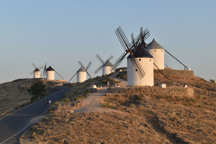 Traditional windmill on landscape against clear sky
