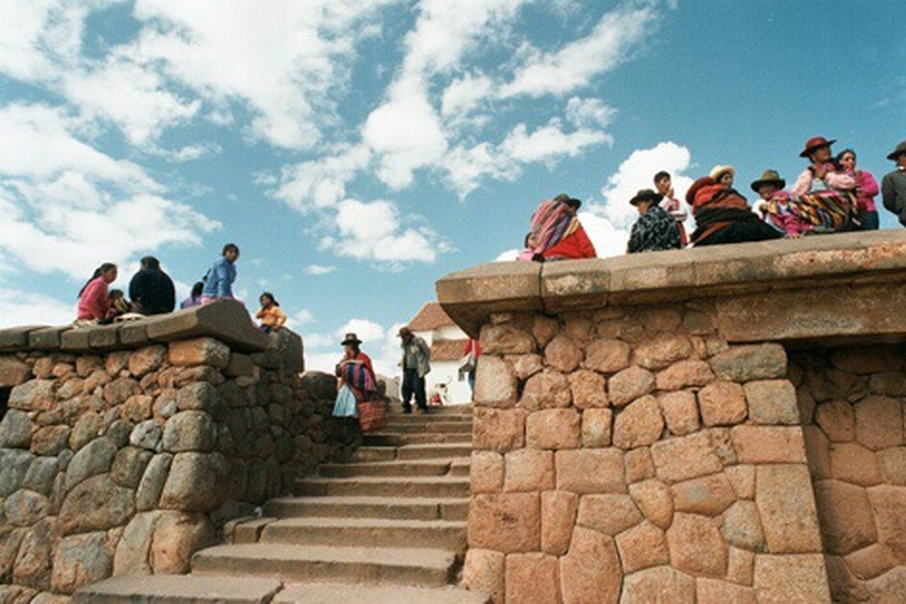 LOW ANGLE VIEW OF PEOPLE ON STAIRS AGAINST SKY