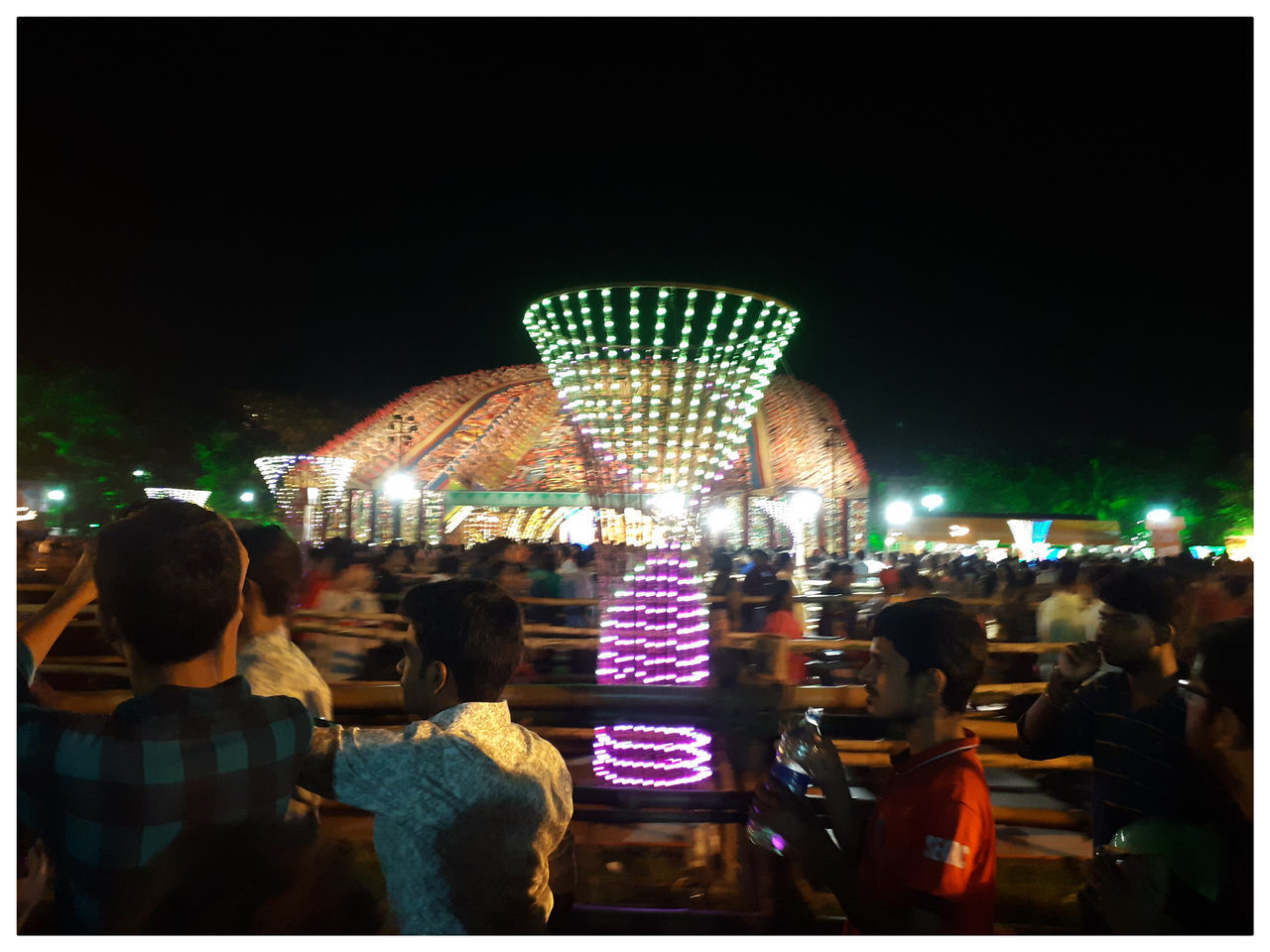 REAR VIEW OF PEOPLE AT AMUSEMENT PARK