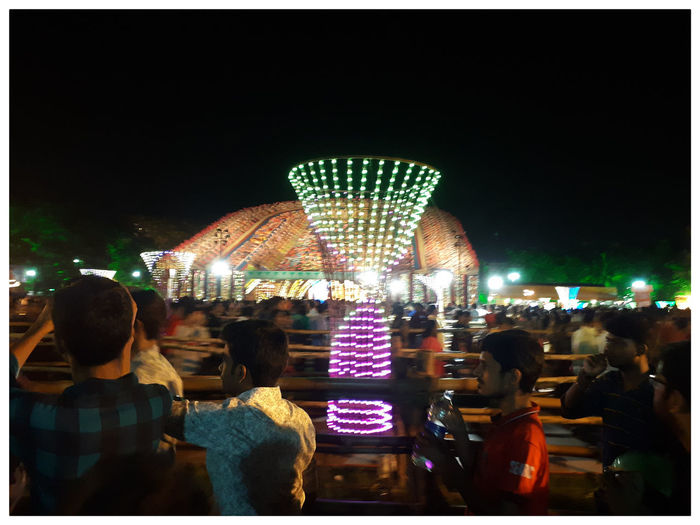 Rear view of people at amusement park against sky at night