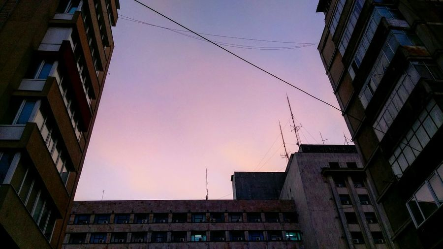 Every time I walk this street, I feel tiny. Low Angle View Building Exterior Built Structure Architecture Sunset Sky City No People Outdoors Urban Urban Lifestyle Urbexphotography Skylovers Pinksky Buildings Bucharest Beautiful Bucharest