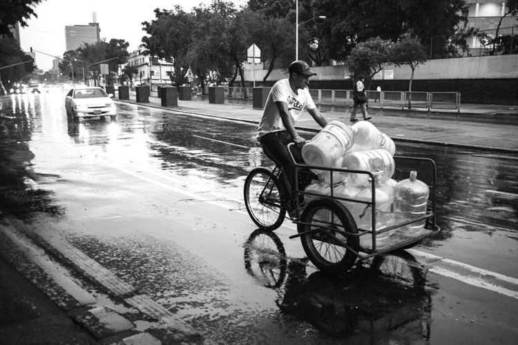 Carring water under water. Streetphotography Reflections Street On The Road Rain Bicicle Water_collection Monochrome Blackandwhite EyeEm Gallery