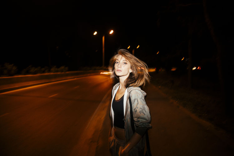Young Woman Standing On Road Against Sky At Night