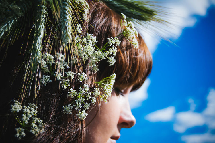 Close-Up Of Flowers On Woman Head Against Blue Sky During Sunny Day