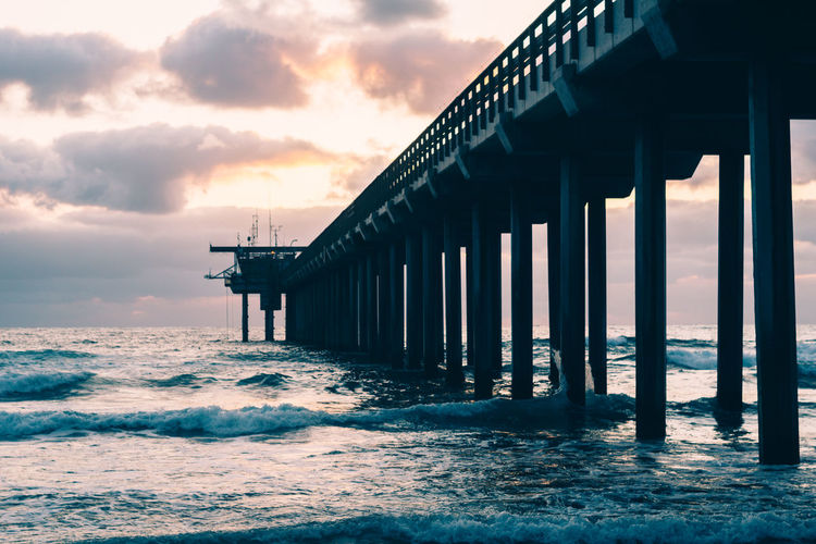 Pier on sea against cloudy sky during sunset