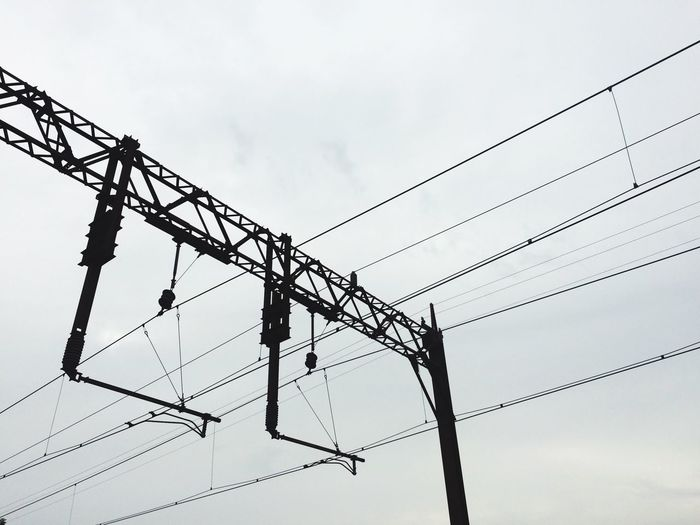 Low angle view of silhouette power lines against sky at dusk
