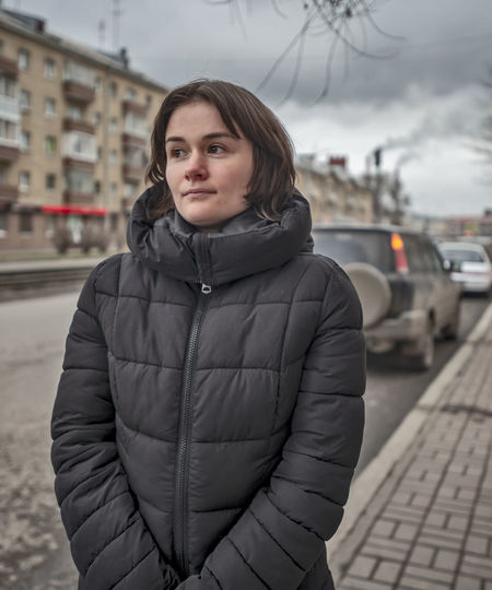 Portrait of woman standing in city during winter